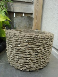 Hypertufa - like concrete but lighter.  DIY planters, sculptures, etc. are online under this name.  This planter was made from the inside of a wicker basket.  I like this one.