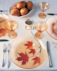 Fall Leaf Clippings. For a splash of style, adorn your table with autumn's brightest accessories: vivid fall leaves. Simply clip sprays of young leaves from a tree in your yard (ours are from a maple). Arrange the clippings at each place setting, and top with transparent glass plates. Come dinnertime, you'll be basking in the oohs and aahs of your guests #thanksgiving #thanksgivingtables #thanksgivingideas #thanksgivingdecor