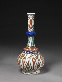 Bottle   Iznik, Turkey, ca. 1545   Fritware, underglaze polychrome painted, glazed   Long-necked bottle with decoration in thickly applied red bole; reciprocating design on body and upper neck looks like teardrop shapes with pointed lobes   VA Museum, London
