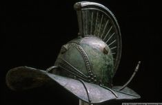 """A bronze, fully intact, undamaged Gladiator helmet featuring the hero Hercules on the front and the Nemian Lion, who he defeated, on the base of the comb. In the collection """"Warriors of the Ancient World"""" at the Higgins Armory Museum. Roman Artifacts, Historical Artifacts, Ancient Artifacts, Art Romain, Roman Gladiators, Roman Helmet, Ancient Armor, Roman History, Ancient Romans"""