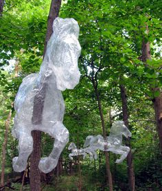 Stunning horses made out of packing tape, installed on trees like a forest carousel.