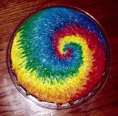 Tie Dye Cake - This was done by loading on the icing in a general shape of the swirl and then blending with a paintbrush.  The sides are a continuation of the top colors.  When I was done I loaded a pastry bag with stripes of all the colors and piped a few rosettes around the bottom.