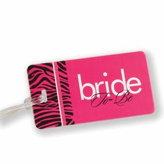 """Bride to Be Zebra Print Luggage Tag made of sturdy and thick fuchsia plastic.  There is a clear sleeve on the back for the address card.  It also includes a clear plastic strap to secure to your luggage. The left side of the luggage tag is printed with a black zebra print. The center of the luggage tag is printed in white and black with the phrase """"bride To-Be""""."""