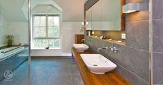 Das Baufritz Landhaus Steinhauser besticht durch das chice und kontrastreiche Bad mit anthrazitfarbenen Fliesen, eleganten Waschtischen und Elementen aus Nussbaum und Glas.