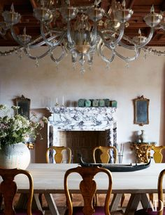 A murano-glass chandelier by Seguso presides over the dining room. Custom bleached walnut table by L'Artigiano Studio; 18th-century Italian chairs; bronze boat sculpture by Edouard Marcel Sandoz.