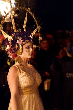 The May Queen, Beltane, Edinburgh. The May Queen is a girl crowned with flowers who is selected to ride or walk at the front of a parade for May Day celebrations. She wears a white gown to symbolise purity and usually a tiara or crown. Her duty is to begin the May Day celebrations.