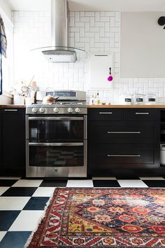 IKEA kitchen cabinets with Semihandmade fronts. Love the rug on classic checkered linoleum floor
