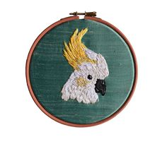 From Scottish artist Hoop&Bone, this artwork features a friendly cockatoo hand embroidered onto aqua blue raw ossian silk, framed in a bespoke coral Embroidery Hoop Art, Floral Embroidery, Cross Stitch Embroidery, Embroidery Patterns, Creative Embroidery, Wooden Hoop, Sewing Art, Tropical Birds, Cockatoo