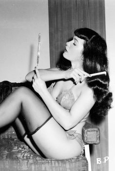 The most famous Vixen of all: Bettie Page combs her silky hair, C. mid-1950's. Photo by Irving Klaw.