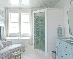 shell display on the shower stall ledge adds to the beachy feel of this bathroom