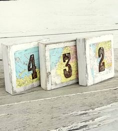 Wooden Map & Metal Table Numbers - Charming for the world traveling couple or at a destination wedding, these wooden table numbers are a rustic roadmap for your guests.