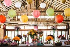 Mesa do bolo colorida decorada com lanternas japonesas em amarelo, laranja, verde e branco. Na mesa, flores roxas e amarelas e docinhos em embalagens rosa e azul. Foto: Frankie e Marília.