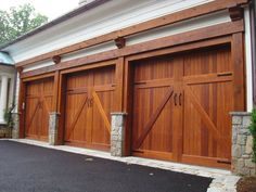 Garage Doors - Nice detail all around here! Beautiful wood doors and trim mixes well with the texture of the stone bases and edging. Garage, ideas, man cave, workshop, organization, organize, home, house, indoor, storage, woodwork, design, tool, mechanic, auto, shelving, car.
