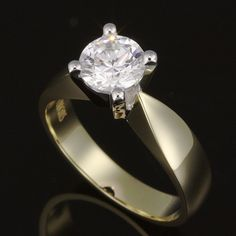Prong set diamond solitaire with inward tapered raised solid shoulder band. Classic perfection - flowing tapered lines enhance an open prong set solitaire Diamond.   Try on this design in our showroom.