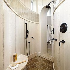 Think outside the box when planning a doorless shower. Looking beyond the expected resulted in this distinctive doorless shower design packed with pampering fittings and handsome tile treatments. Mosaic tiles create horizontal stripes that contrast with the room's curves while underscoring the wall height. An arched doorway and curved bench mirror the hall-like shower's bowed geometry.