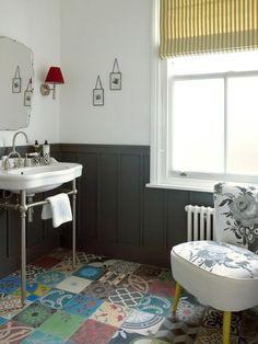 Badezimmer mit Vintage Armatur und unterschiedliche bunte Fliesen am Boden