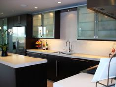Dark wood cabinets with handles, white countertops, frosted glass uppers.