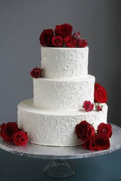 White scrolled wedding cake with red roses