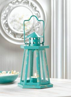 Lighthouse Candle Lantern What could be more perfect than a pretty lighthouse lantern finished in aquamarine blue? This charming lighting accent is ready for the candle of your choice and you can hang