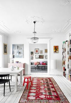 This bright and colorful living room with great paintings and a patterned rug is fantastic. The stuccoed ceiling and chandelier adds an elegant touch.