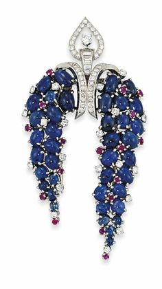 AN SAPPHIRE, RUBY AND DIAMOND CLIP BROOCH, BY BULGARI The central brilliant and baguette-cut diamond openwork panel of Arabesque design, suspending two trailing cluster panels of cabochon sapphires interspersed with brilliant-cut diamond and circular-cut ruby highlights, second quarter of the 20th century, 7.7cm long, original fitted maker's case Signed Bulgari