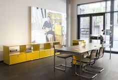 USM Haller Sideboard in golden yellow with glass inlays. In the Background Max Guderian, a Student from the hfg in Karlsruhe. In the front USM Haller table.