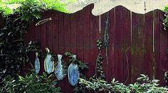 Prkenný plot má horní okraj zvlněný jako vodní hladinu, dojemdokreslují zavěšené keramické ryby