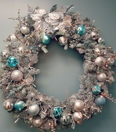 Christmas Wreath, Flocked with silver and ice blue ornaments. Silver Poinsettias adorned with snowflakes and silver berry accents. Set of 200 lights with Plug. Ideal for Accent walls or fireplaces. Wr