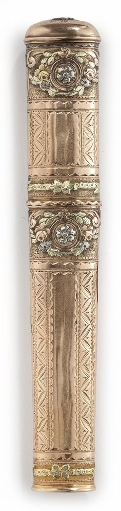 A CONTINENTAL THREE-COLOR GOLD NEEDLE CASE, LATE 18TH CENTURY of oval outline, bright-cut and chased borders of vari-color gold flowers surrounding rosettes<br> <em>maker's mark only not clear</em><br> length 4 7/8 in.<br> 12.4cm