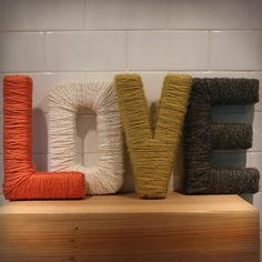 yarn wrapped around cardboard letters.