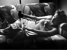 Woman relaxing on sofa, reading & drinking a Coke. Arizona, 1952.