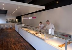 white counter. glass showcase. white wall. neon accents. wood floors. black and white colourblock ceilings.