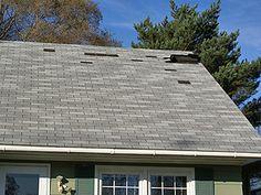 Asphalt shingle roof with wind damage, broken, loose and missing shingles.