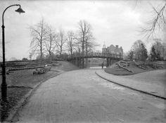 """Houten brug in het Hunnerpark. Op de achtergrond """"Belvoir"""", ca. 1935."""