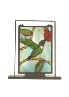 9.5 Inch W X 10.5 Inch H Hummingbird Lighted Mini Tabletop Window - 9.5 Inch W X 10.5 Inch H Hummingbird Lighted Mini Tabletop WindowYou will think you're walking through a lively botanical garden on a refreshing springtime morning with this Hummingbird tabletop window. Handcrafted and designed of authentic stained glass the miniaturetabletop window is illuminated from the back and makesa charming decorative accent. Theme: FLORAL ANIMALS Product Family: Hummingbird Product Type: NOVELTY…
