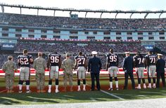 Patriots players, coaches, Robert Kraft & more joined with over 100 service members from all branches of the military to present a field-sized flag