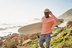 A young Black surfer walks along a scenic rocky coastline looking for surf. He is carrying his surfboard. Stylist: Bielle Bellingham Photographer: Micky Wiswedal Model: Mandla Ndlovu Young Black, Walks, Surfboard, Surfing, Stylists, African, The Unit, Stock Photos, Model