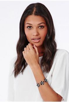 Bring a sweet addition to your look with this stunning bracelet. With three flower shape designs filled with grungy black gems and clear crystals on a dark metal chain - sure to enhance any outfit.