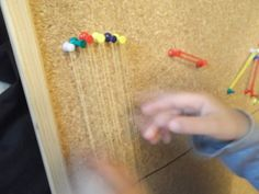 Music on a corkboard - Fine motor skills activity for children to make music with pins and rubber-bands. Practice language for colours, shapes, and so much more vocabulary!
