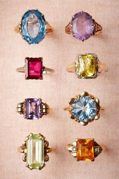 A collection of vintage costume jewelry rings with colored crystal stones