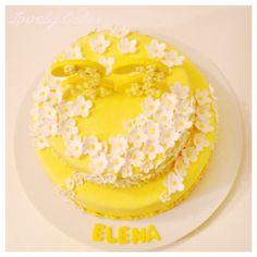 Tarta amarilla con flores blancas