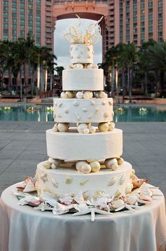 For an elegant seaside wedding, sugar shells adorn layers of a sandy-hued cake surrounded with shells and starfish.