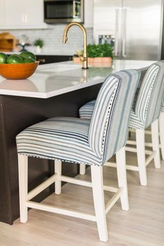 For casual dining or snacking, three bar stools upholstered in ticking stripe fabric stools belly up the island. The patinated gooseneck faucet is both functional and acts as a focal point.