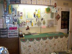Linda M. Thielfoldt's sewing room - this is my cutting table - made it from an unfinished interior door placed on workbench legs.  Skirt covers my wire storage drawer units and my fabric stash. Note design wall behind door, shelf above and you can see that every inch of my small room is in use.