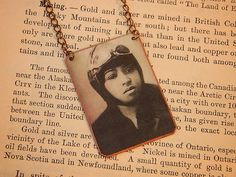 "Bessie Coleman was the first African American female pilot, and the first African American, male or female, to hold an international pilot's license. She made her living as a ""barnstorming"" stunt pilot, and became quite well known around the world. To celebrate her heroics in the air and in history, you can wear this lovely necklace with her image on it created by Sarah Wood."