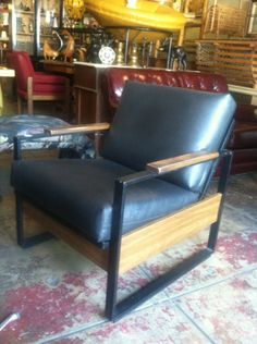 The base of these vintage 1960s club chairs were crafted with metal to resemble wood panels while the cushions are made of 100% naugahyde. Compact and comfortable, this pair of chairs are handsome and smart, just like you.