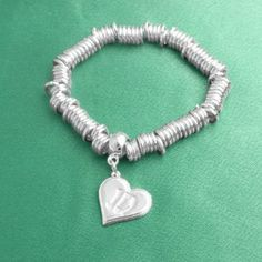 One Direction Loop Charm Bracelet One Direction Official Jewelry. $24.99. Stretchy bracelet. One Direction '1D' Logo Charm. OFFICIAL ONE DIRECTION MERCHANDISE. Save 14% Off!