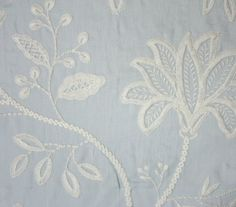 Larkhill Fabric A pale blue fabric embroidered with a large stitch floral design in white.