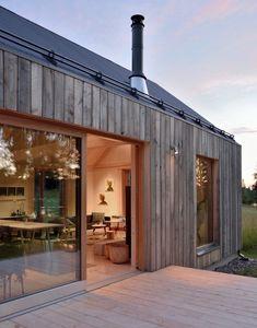 MNY Arkitekter a utilisé sept variétés de bois pour créer cette maison à pignon sur la rive d'un petit lac à Tenala, en Finlande. Les architectes ont donné