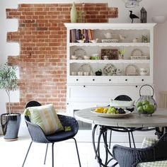 Family kitchen diner with exposed brickwork, white floor tiles, white dresser, grey stone-top table and rattan chairs. In this large kitchen-diner, a partially exposed brick wall and a statement wooden dresser lend a convivial air to the dining area. Read more at http://www.idealhome.co.uk/kitchen/kitchen-ideas/family-kitchen